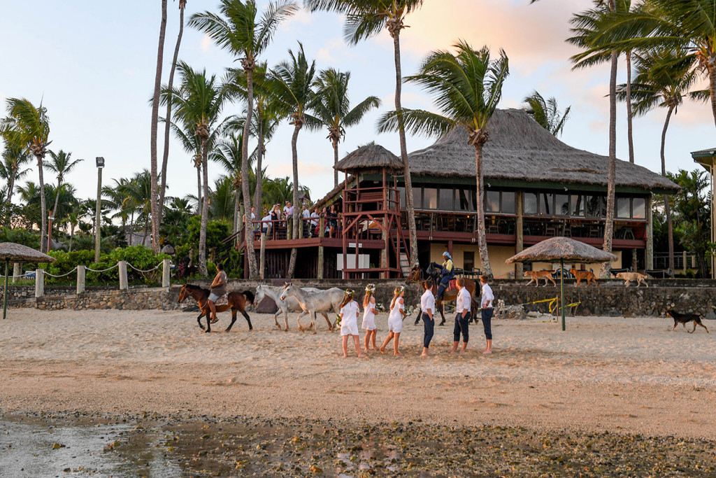Wideshot of Bridal party against Outrigger hotel Fiji at sunset