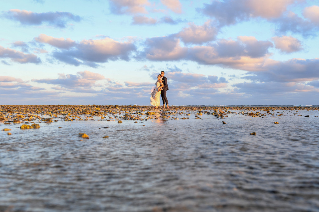 Wideshot of bride and groom in the ocean at sunset