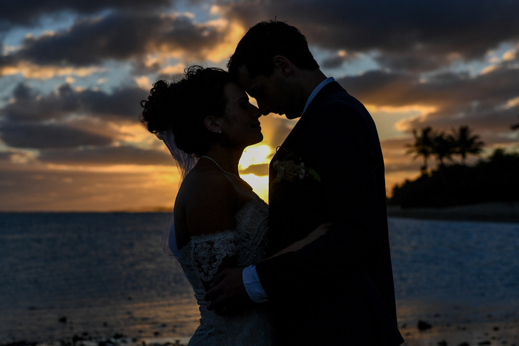 Mid closeup Silhouette shot of bride and groom against fiery sunset in Fiji