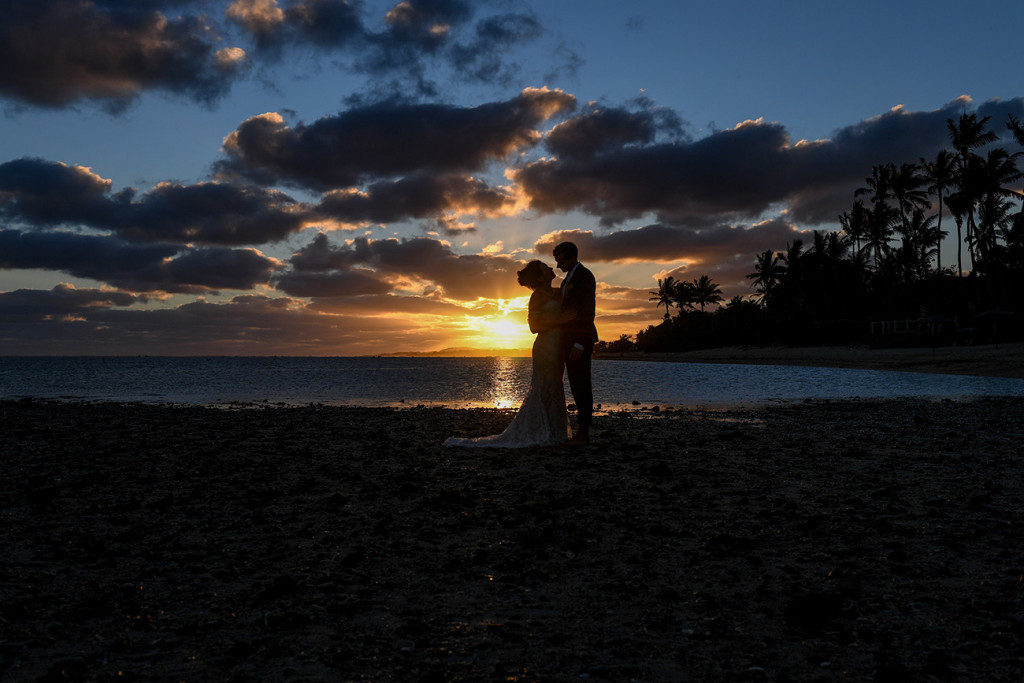 Wide silhouette of bride and groom kissing against sunset