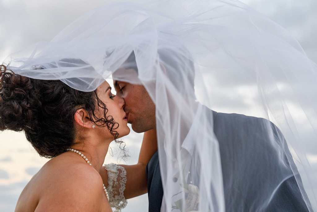 Bride and groom kiss under the veil in boho wedding at the Outrigger Fiji
