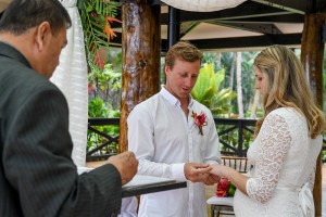 The groom puts the ring on the bride's finger at their elopement in Fiji