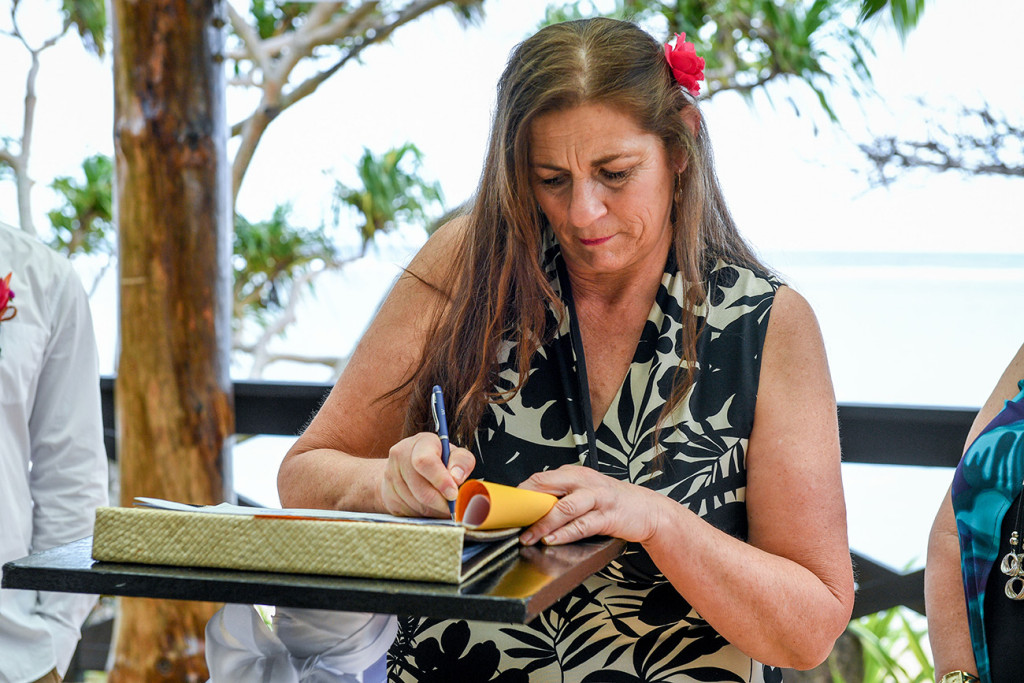 The mother is signing the register for her wedding in Fiji at the Warwick