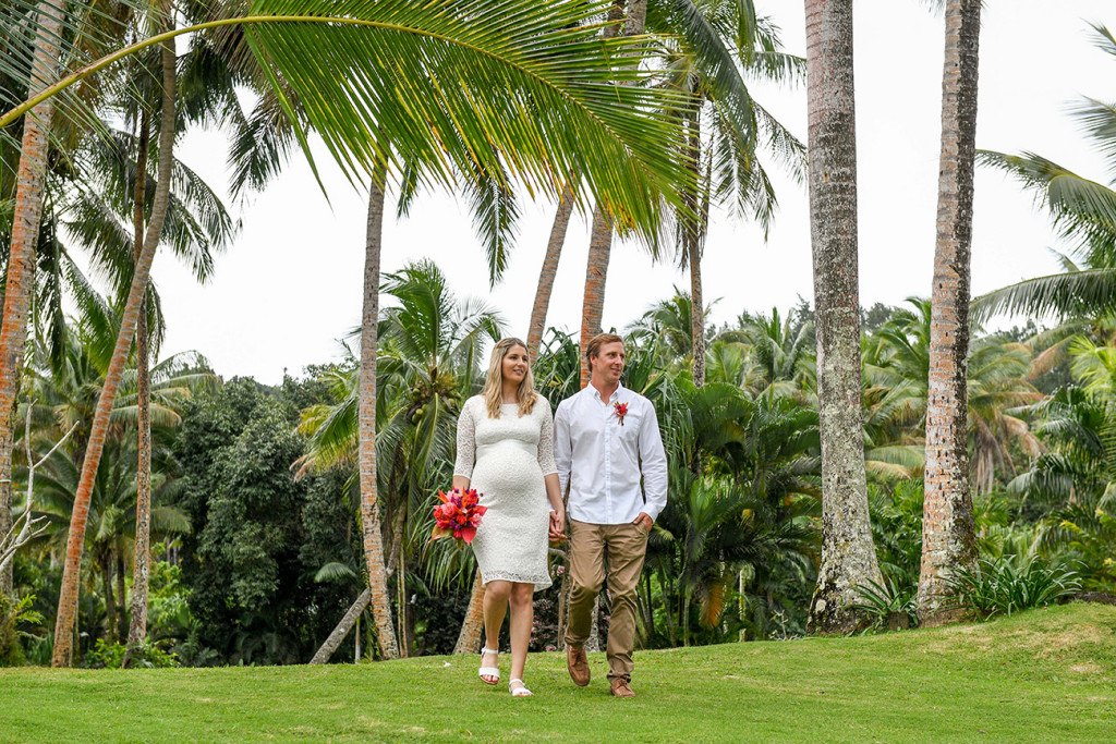 The pregnant bride and groom are walking among the palm trees at the Warwick Fiji