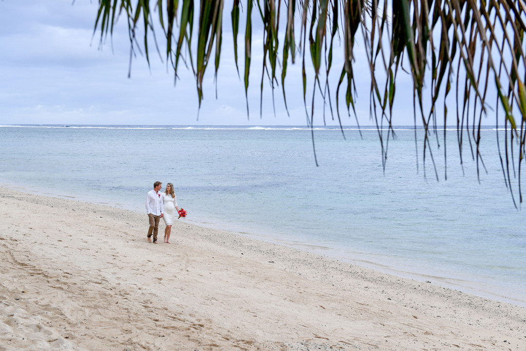 The pregnant bride and groom are walking along the Warwick beach on the coral Coast in Fiji