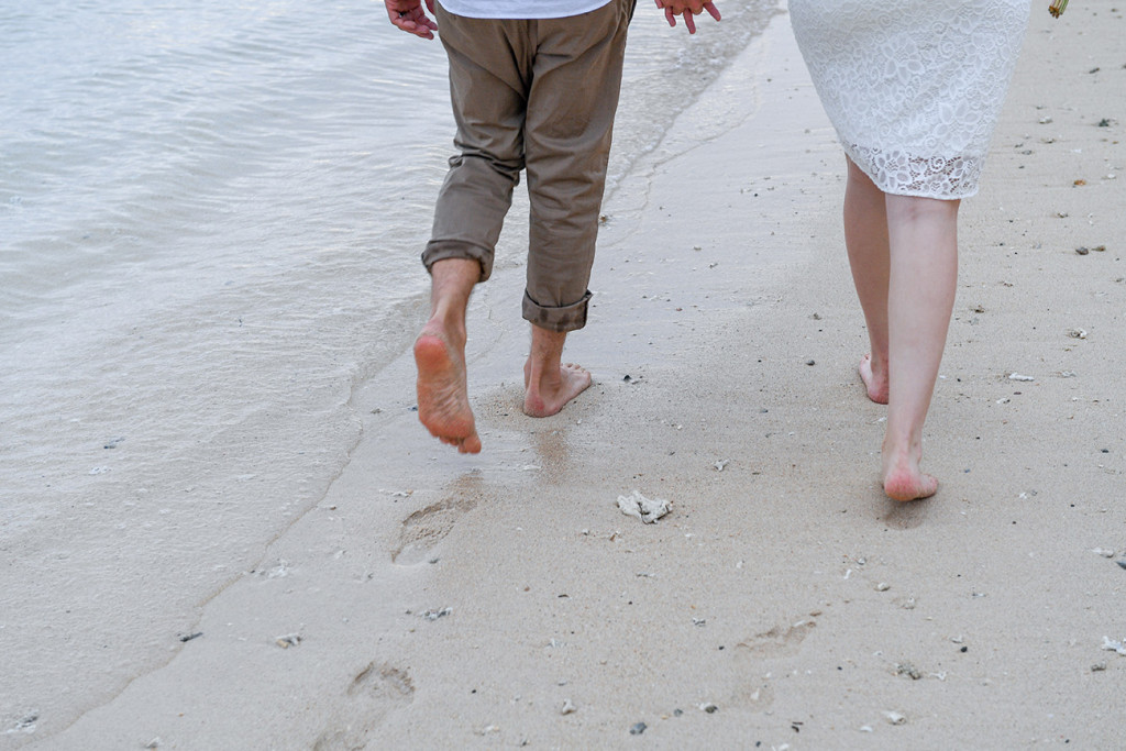 Bride and groom walking bare feet along the beach with clear water in Fiji