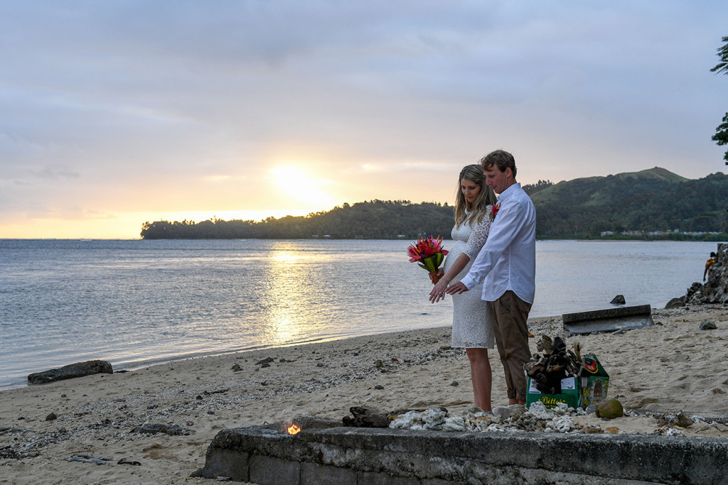 The bride and groom at sunset on the Fiji beach by a bonefire