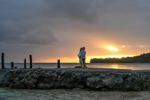 The bride and groom at sunset on the Fiji beach looking at the horizon