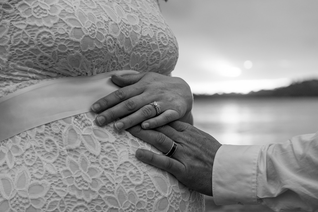 The bride is touching the belly of his pregnant wife balck and white photograph in Fiji