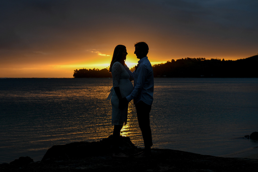 Silhouette of the bride and groom by a sunset on fire in Fiji by the beach
