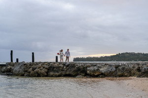 Bride and broom are walking along the jetty at the Warwick