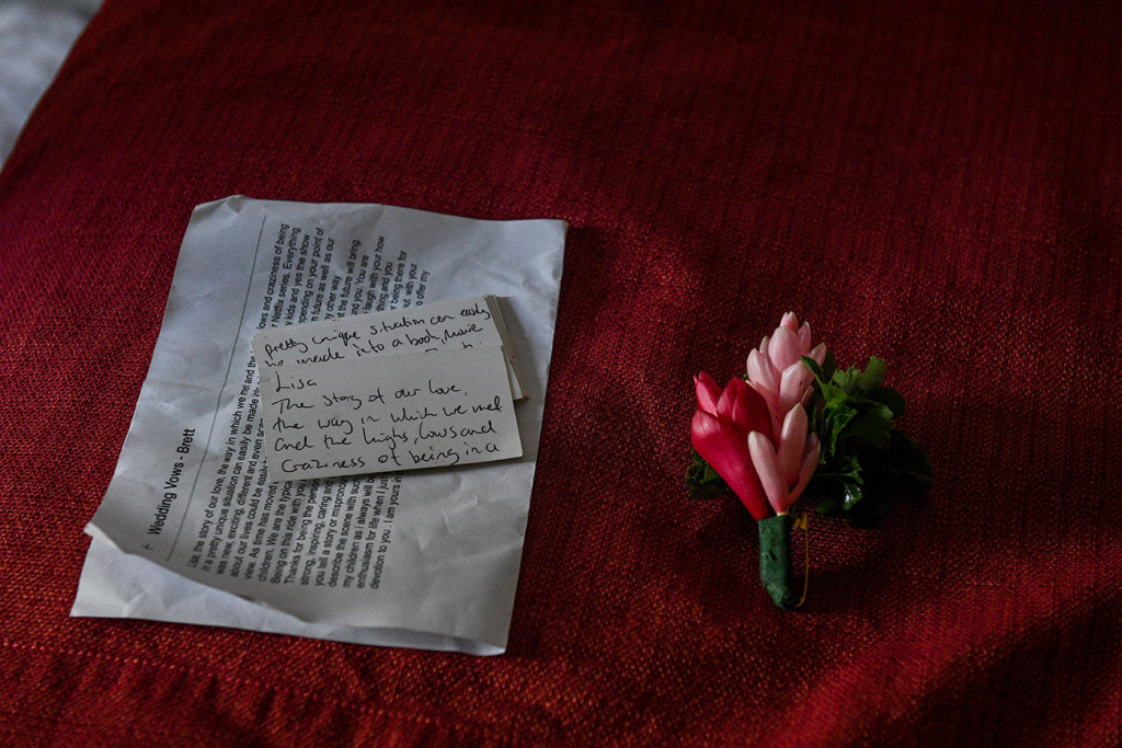 Groom's handwritten vows beside pink flower boutonniere