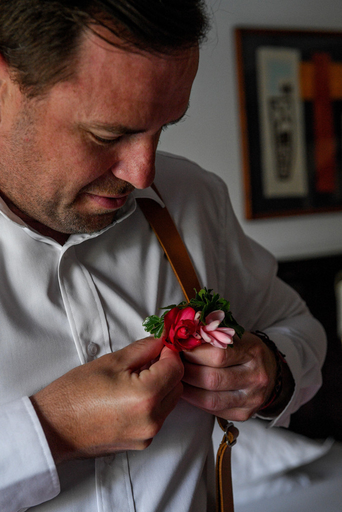 Groom adjusts pink tropical flower boutonniere on his suspenders