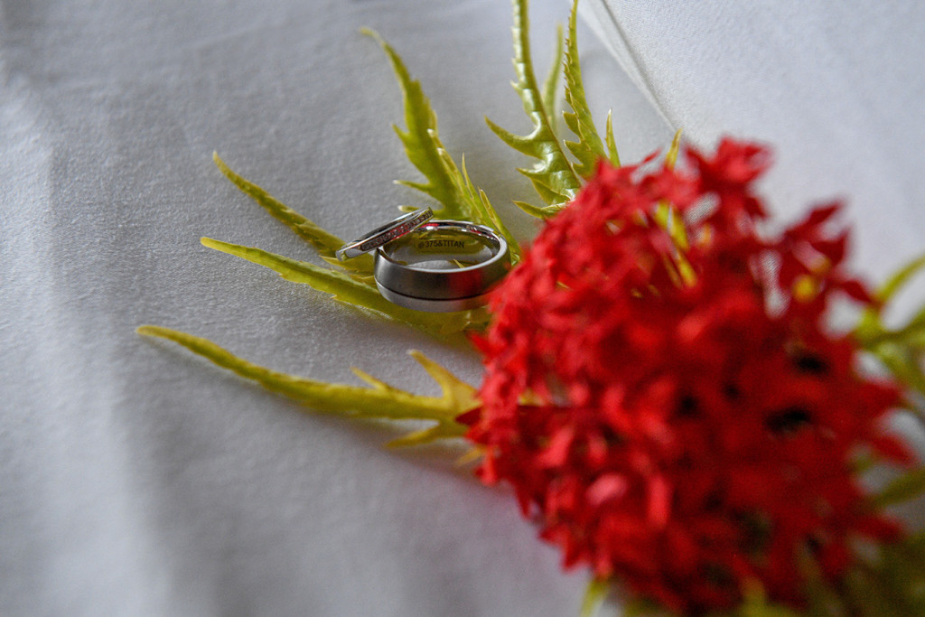 Silver diamond rings by Christopher & Co against crimson tropical flower bouquet