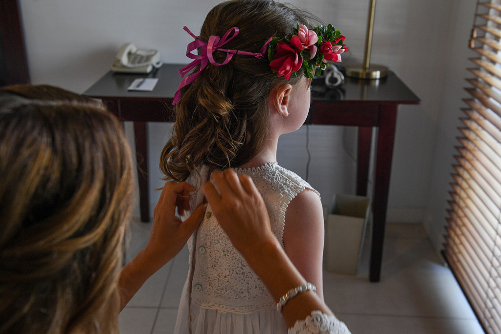 A bridesmaid zips up a flower girl's dress