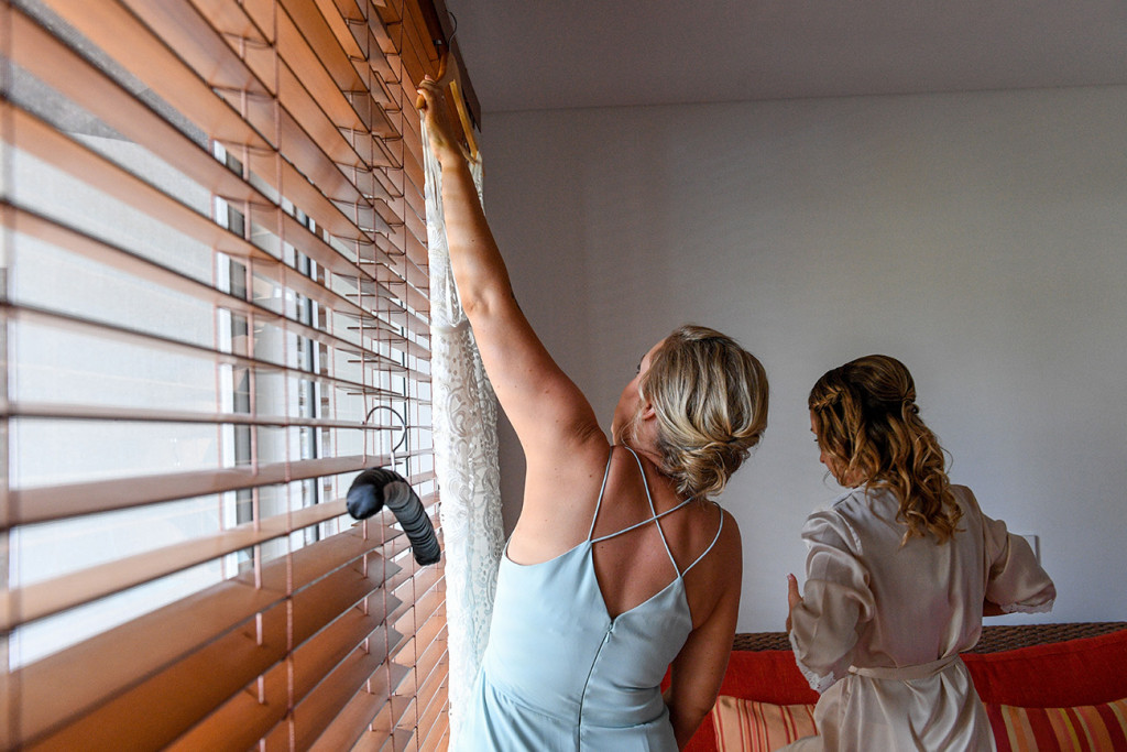 Bridesmaid adjusting blinds in hotel room at Sheraton Denarau Fiji