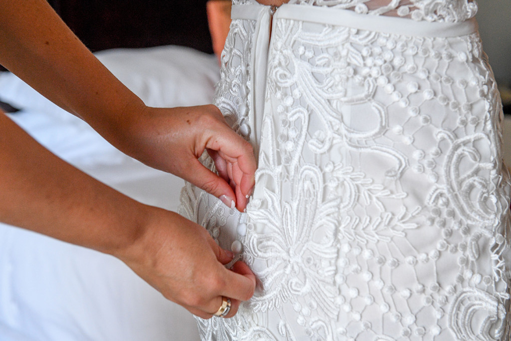 Closeup detail of wedding dress being zipped up
