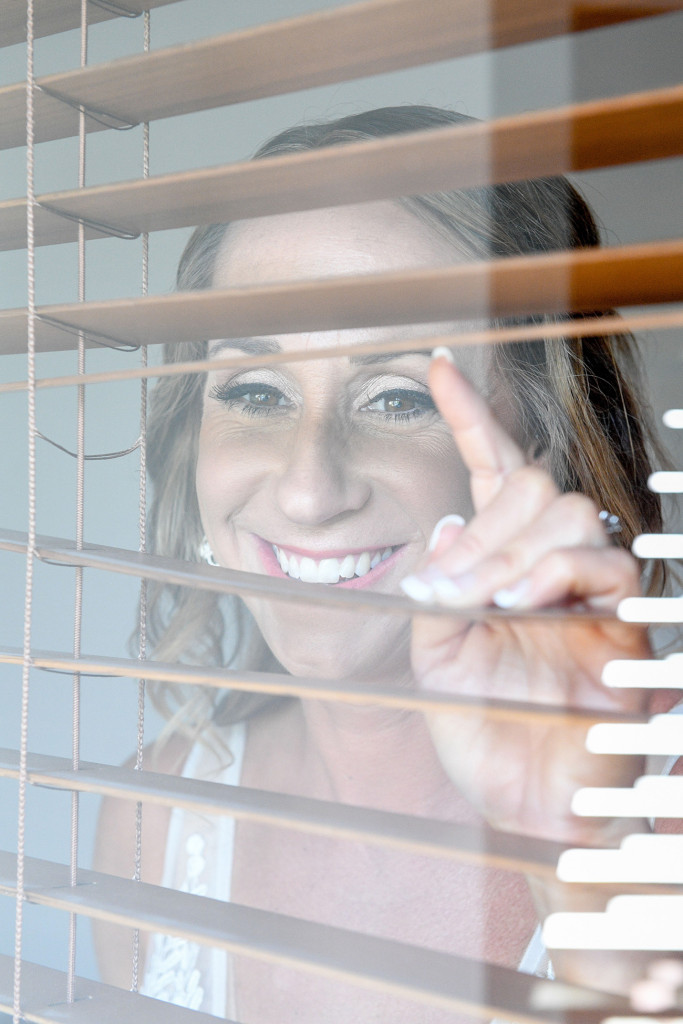 Stunning smiling bride peeps through the blinds at the Shearton Hotel Denarau Fiji