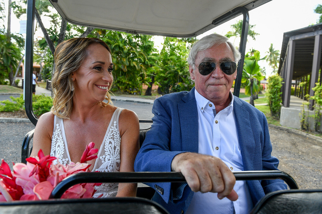 Smiling Bride and her father seated in a golf cart enroute wedding venue