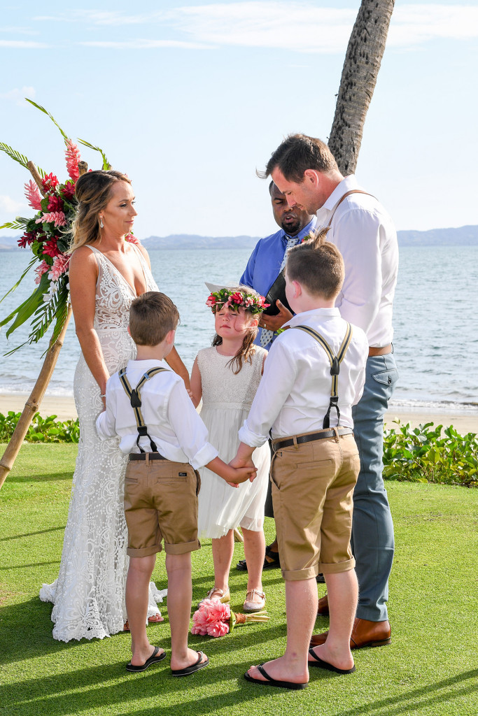 The bride, groom and children hold hands at the altar overlooking breathtaking Fiji beach