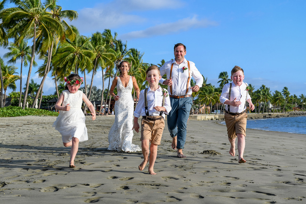 Newly married couple run on black sand beach with their family