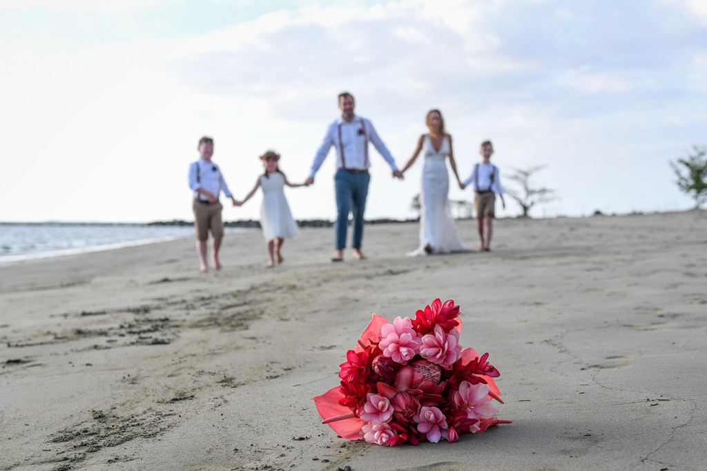 Bride, groom and family hold hands on the beach, tropical floral bouquet sharp in foreground