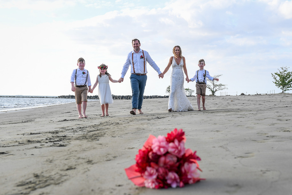 Pink flower bouquet in foreground of family photo at black sand beach