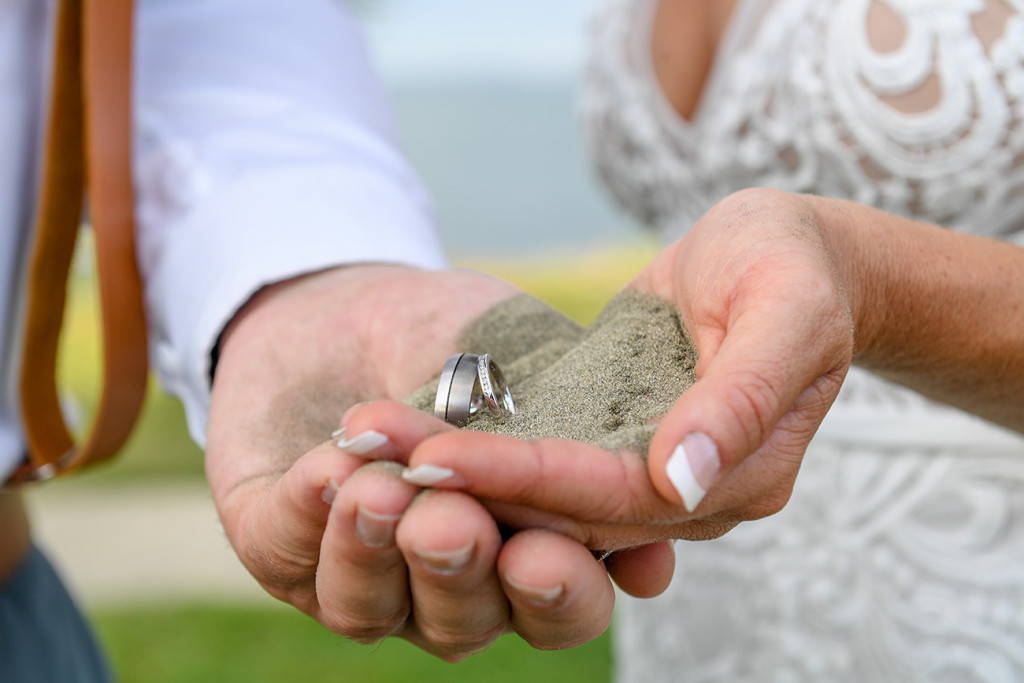 Bride and groom cup their silver and diamond rings in black sand