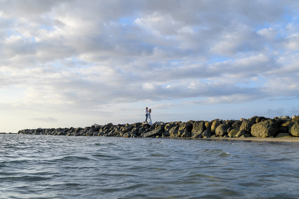 Breathtaking landscape shot of bride and groom on rocky shore in Denarau Fiji