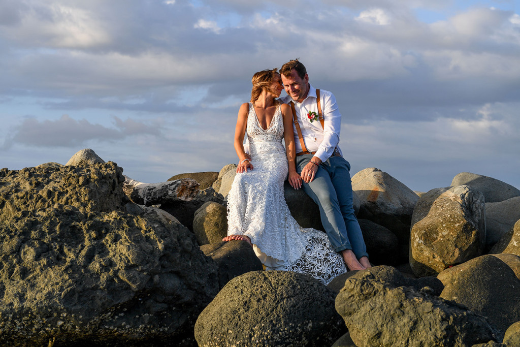 The bride and groom have a moment seated on rocks in the sunset glow of the Pacific ocean