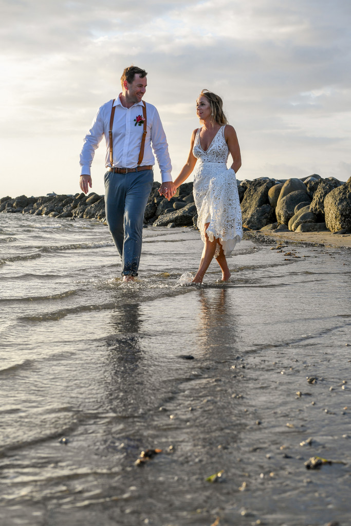 Bride and groom stroll in the shallow waters of the Pacific ocean at sunset in Fiji