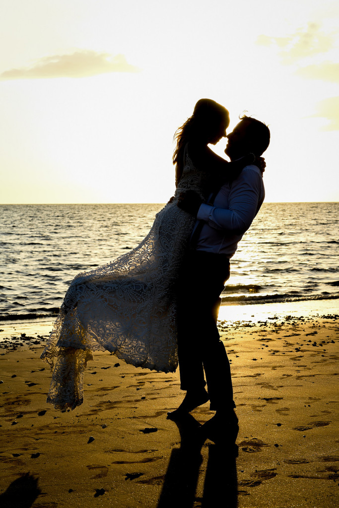 Silhouette of Groom lifting bride against golden Fiji sunset