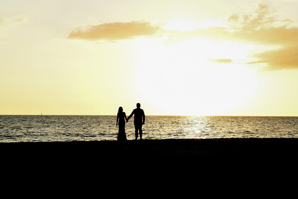 Silhouette landscape photo of bride and groom walking into the sunset of the Pacific ocean