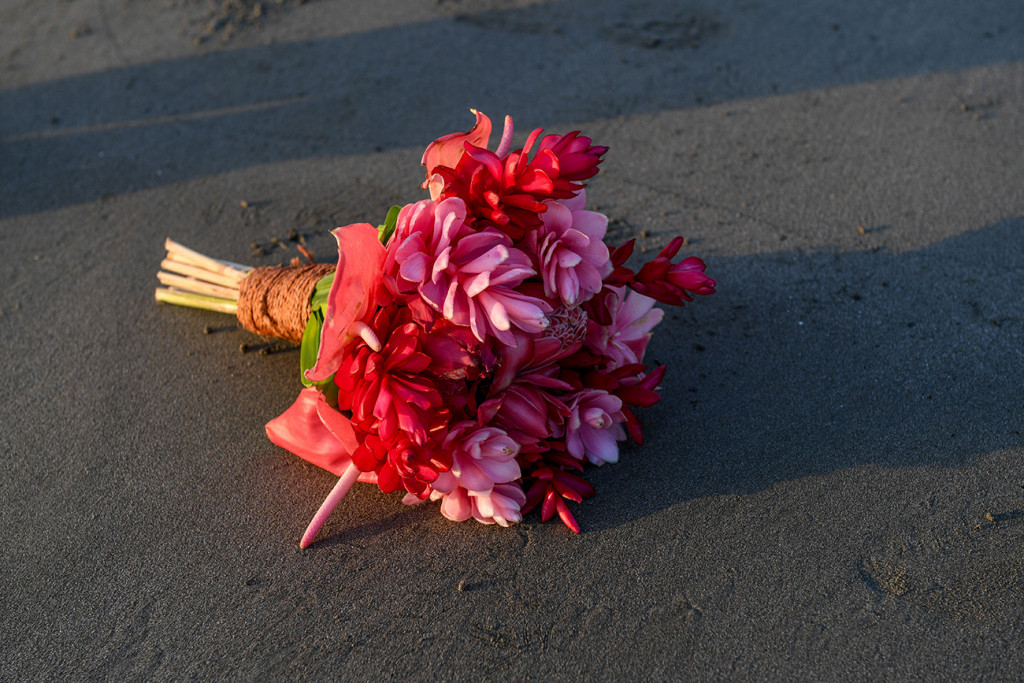 Tropical pink flower bouquet resting on the black sand beach at Denarau Fiji