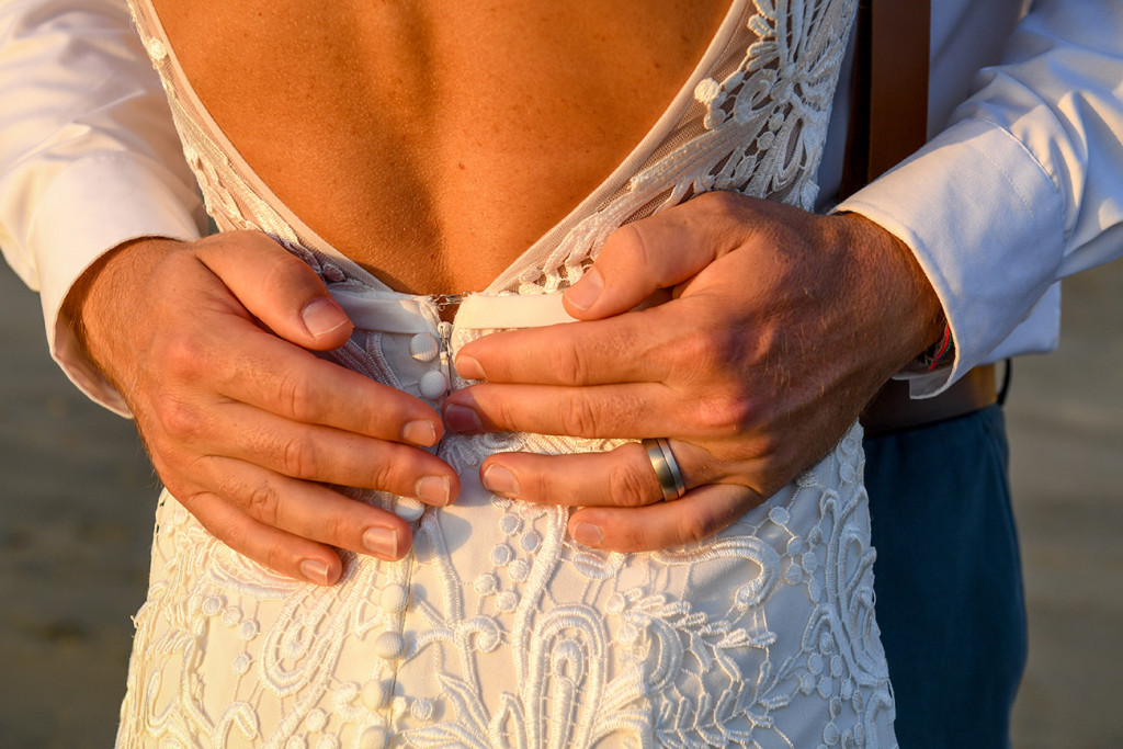 Closeup of the groom's hands holding his bride's waist in the amber glow of sunset