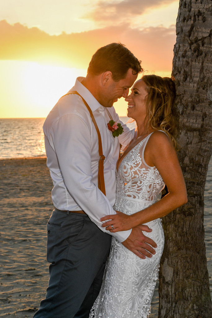 Bride and groom embrace against a palm tree in the golden sunset