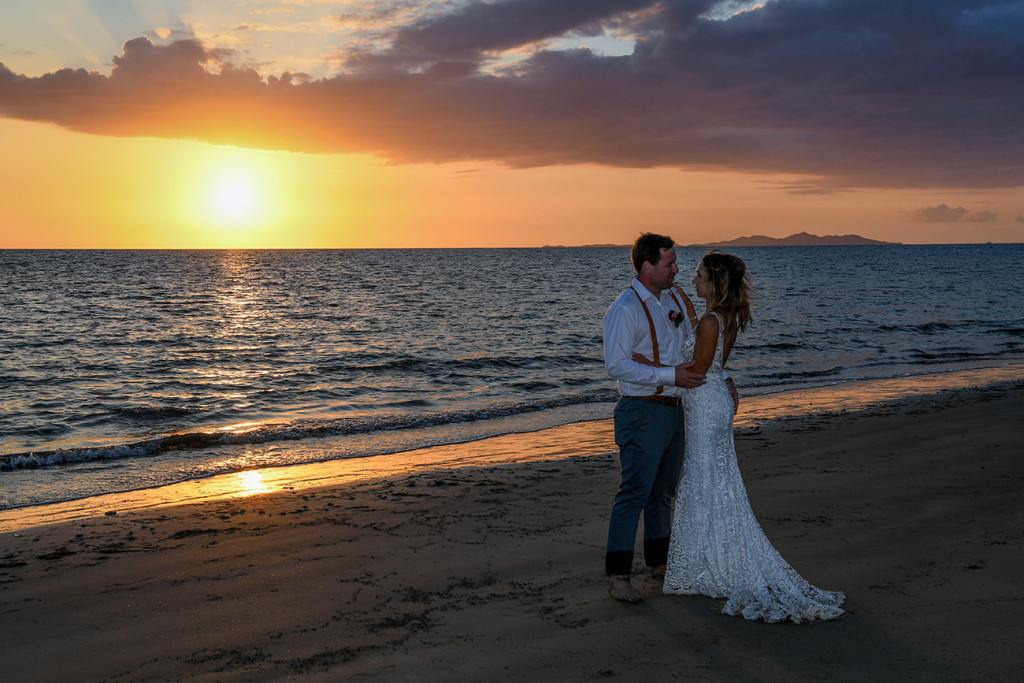 Bride and groom beside the Pacific ocean at sunset