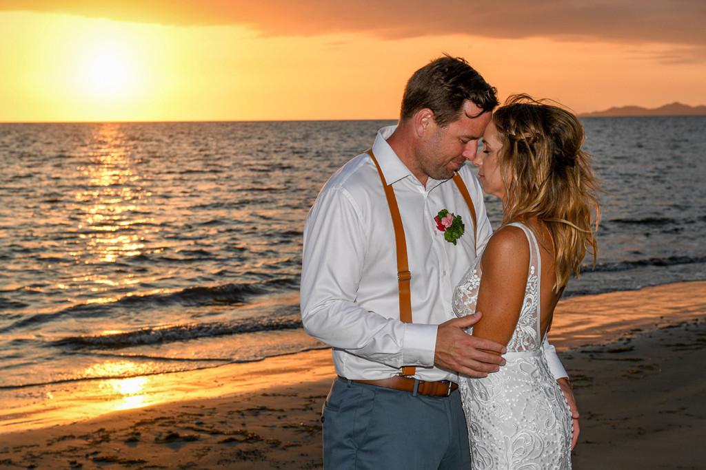 The bride and groom have a moment against the golden sunset over the Pacific ocean