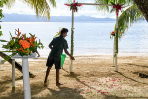Boy throwing rose petals on white sand for the wedding ceremony, at Matangi island resort Fiji
