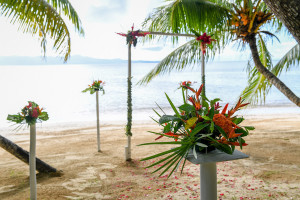 The wedding ceremony set up with an arch and tropcial orange flower at Matangi island resort in Fiji