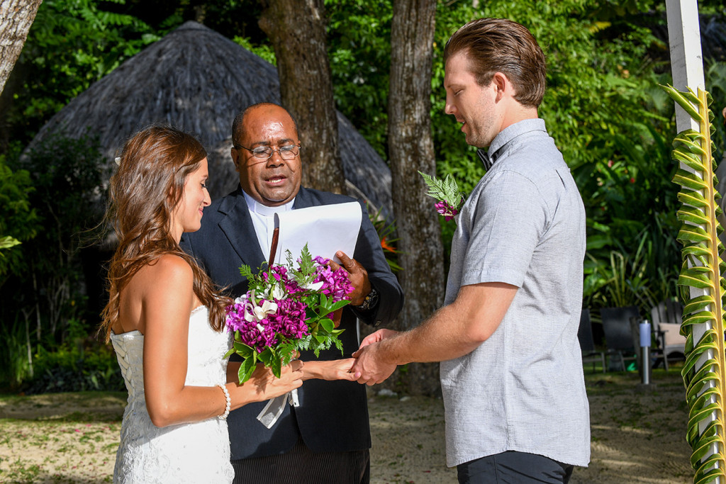 Groom puts the ring at the bride's finger at the wedding ceremony, Matangi island in Fiji