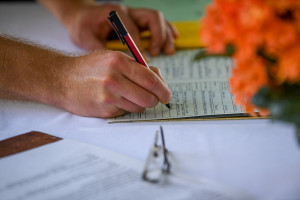 Signature of the wedding certificate close up on the groom's hand, Matangi island resort in Fiji
