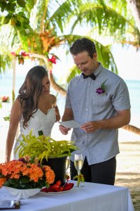 The young married couple is looking at their marriage certificate at Matangi island resort in Fiji