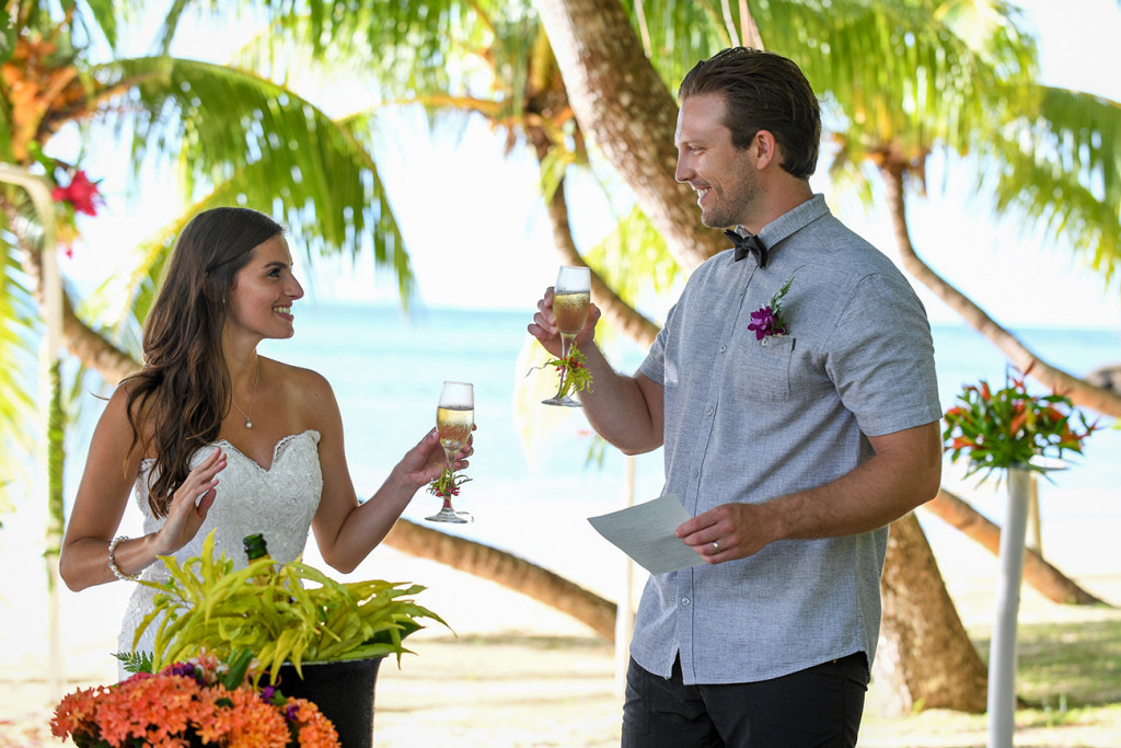 The young married couple cheer with a glass of champagne at Matangi island resort in Fiji