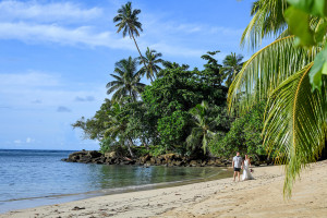 bride and groom walking along the beach, holding hands at Matangi island resort in fiji