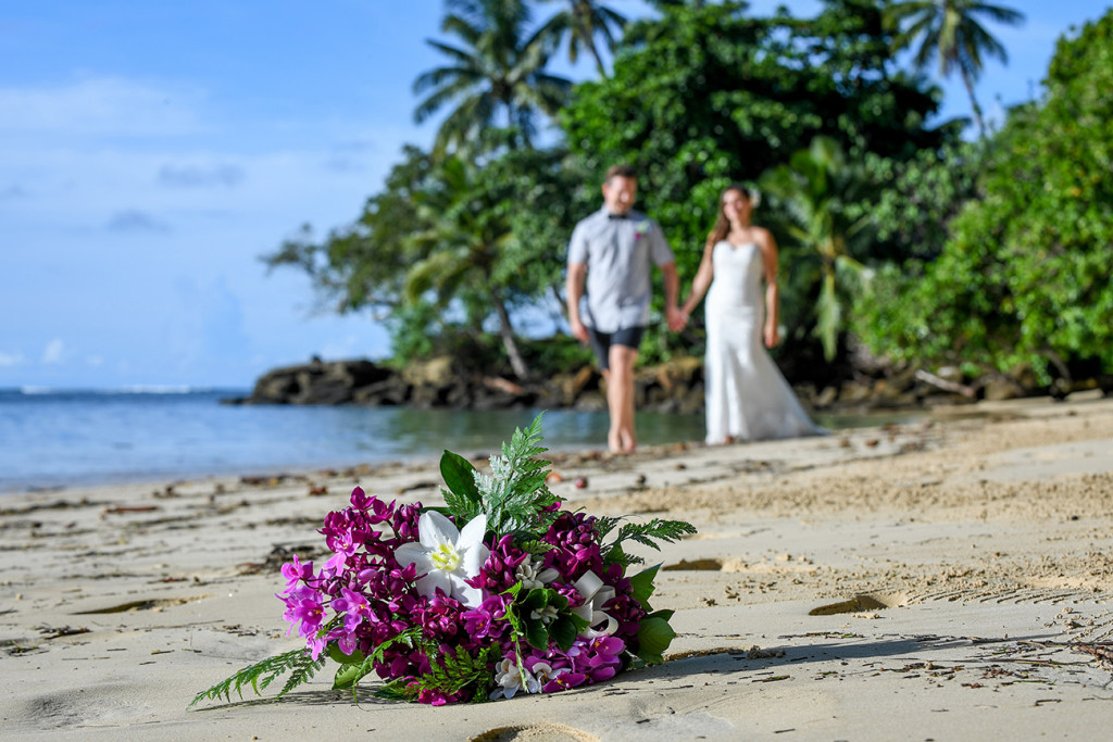 Bride and groom walking with their bouquet in the foreground, Matangi Fiji