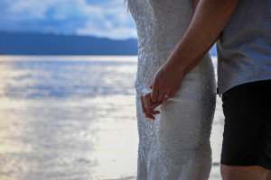 Hands of the bride and groom with their rings and sea in the backgroup, Matangi island resort in Fiji