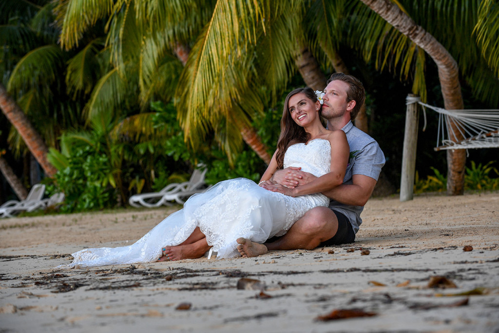 Bride and groom telling eachothers a secret, Matangi island resort in Fiji