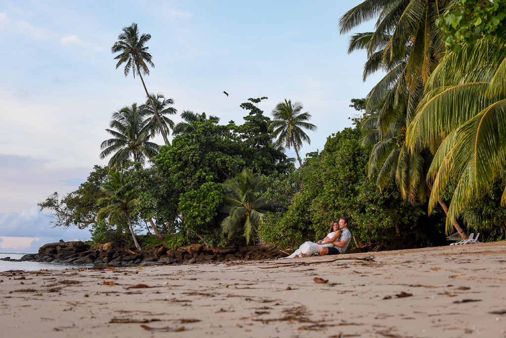 Engaged bride and groom sited on the beach looking at the sea, Matangi Island resort, Fiji