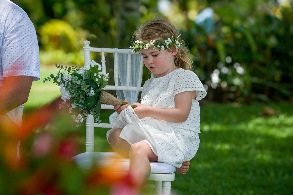 Flower girl plays with her dress at